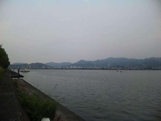 夕暮れの湖岸で笛